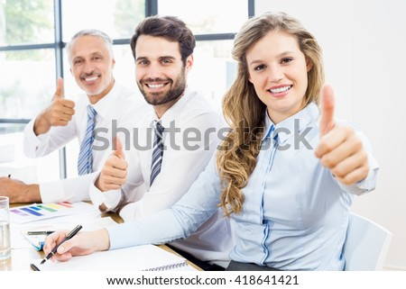Business colleagues showing thumbs up in a meeting at office - stock photo