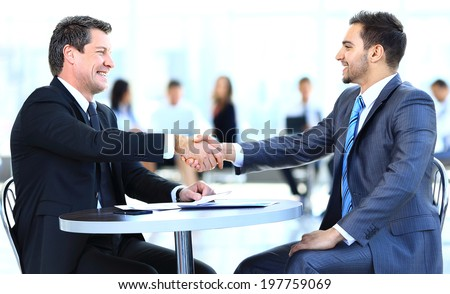 Business colleagues sitting at a table during a meeting with two male executives shaking hands - stock photo