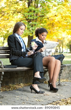 business colleagues sitting on bench in park, business people on break - stock photo