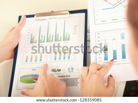 Business colleagues sitting together at table and viewing documents from clipboard - stock photo