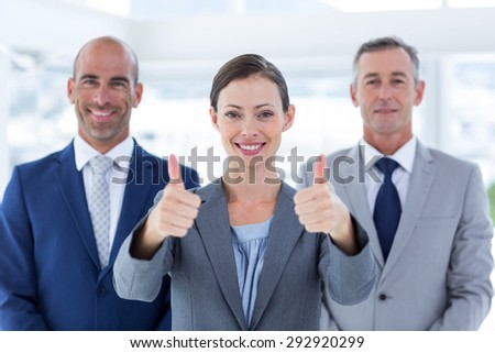 Business colleagues smiling at camera and thumbs up in the office - stock photo