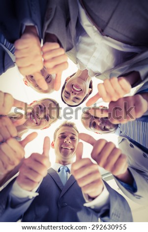 Business colleagues standing in circle and looking at camera in the office - stock photo