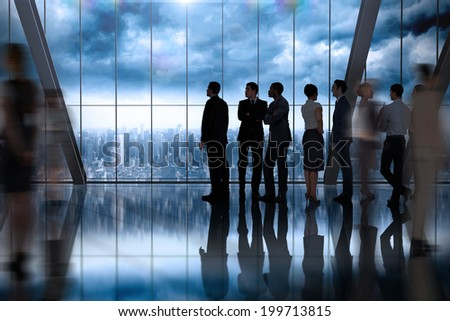 Business colleagues talking against room with large window looking on city - stock photo