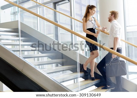 Business colleagues talking on stairs and flirting - stock photo