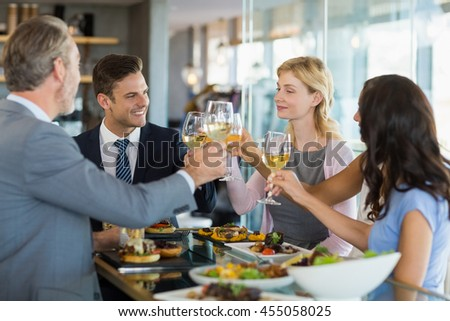 Business colleagues toasting beer glasses while having lunch in a restaurant