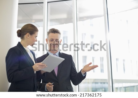 Business colleagues using digital tablet in office - stock photo