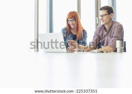 Business colleagues using laptop at desk in creative office - stock photo