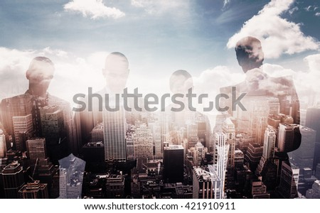 Business colleagues using their multimedia devices against aerial view of a city on a cloudy day - stock photo