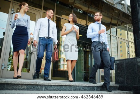 Business colleagues walking outside office and talking