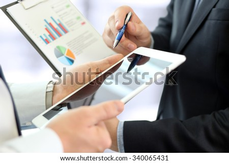 Business colleagues working and analyzing financial figures on a graphs - stock photo