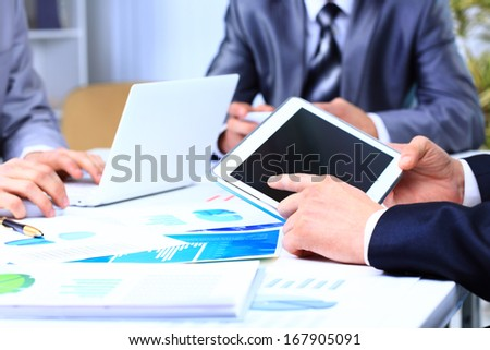 Business colleagues working on a laptop and digital tablet - stock photo