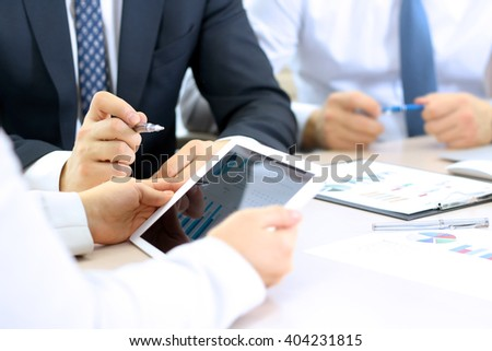business colleagues working together and analyzing financial figures on a digital tablet - stock photo