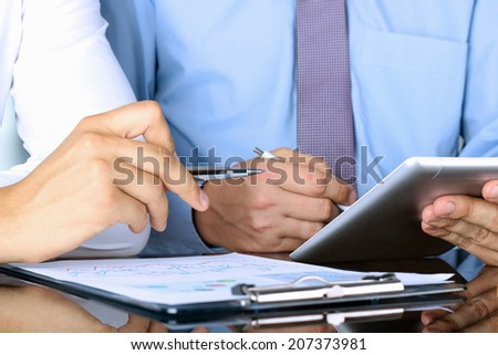 business colleagues working together and analyzing financial figures on a digital tablet and  graphs - stock photo