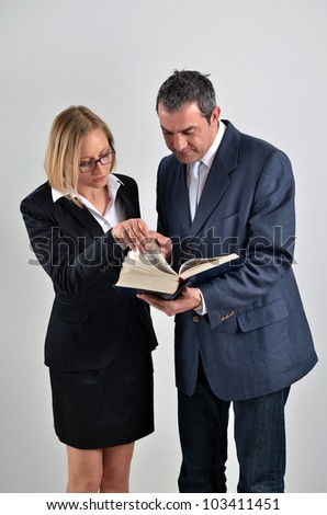 Business colleagues working together and reading a book in a meeting - stock photo