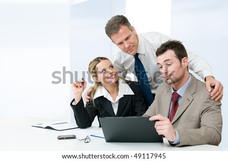 Business colleagues working together during a meeting with mature manager supervising the work - stock photo
