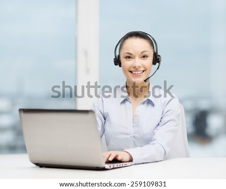 business, communication and call center concept - friendly female helpline operator with headphones and laptop computer - stock photo