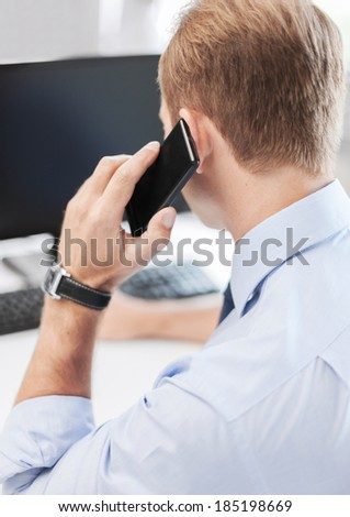 business, communication and technology concept- businessman with smartphone in office - stock photo