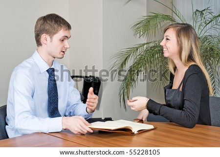 Business communication in office between businessman and businesswoman - stock photo