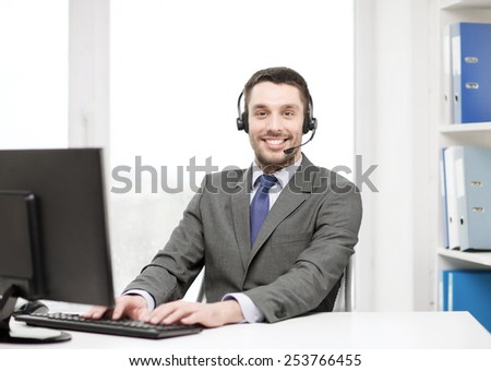 business, communication, technology and call center concept - friendly male helpline operator with headphones and computer at call center - stock photo