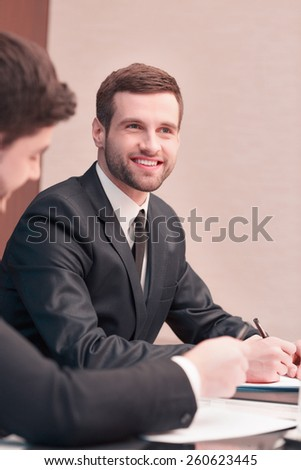 Business communication. Two cheerful business men in suits smiling and talking to each other while sitting in the meeting room - stock photo