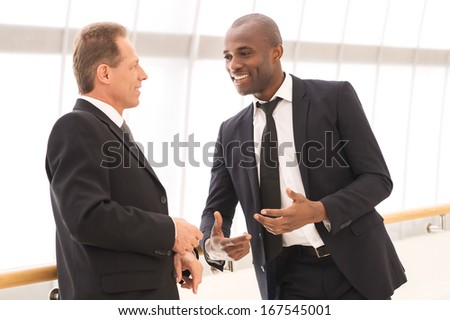 Business communication. Two cheerful business men talking to each other and gesturing - stock photo