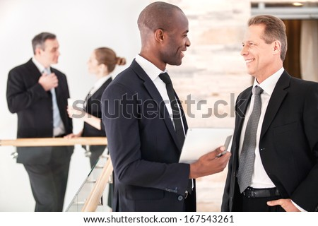 Business communication. Two cheerful business men talking to each other while their colleagues standing on background - stock photo