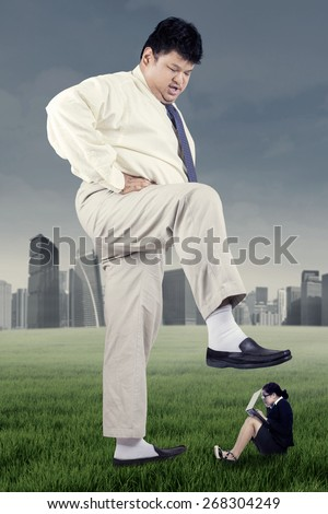 Business competition concept with big businessman trampling female worker - stock photo
