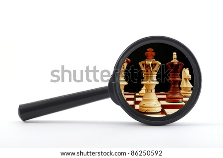 business competition concept with chess pieces and magnifying glass - stock photo