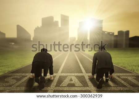 Business competition: Rear view of two worker wearing formal suit and kneeling on the start line to compete - stock photo