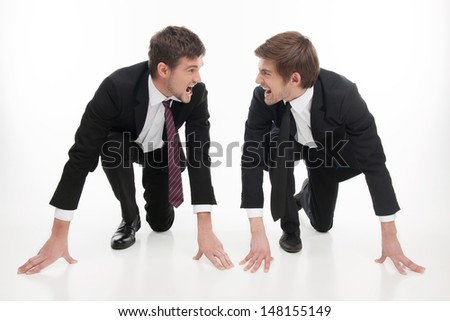 Business competition. Two angry young business people standing at the start line and looking at each other while isolated on white - stock photo