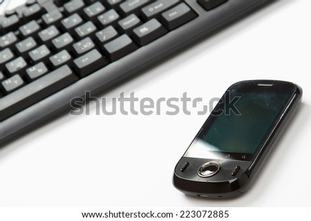 Business concept - a mobile phone near a keyboard - stock photo