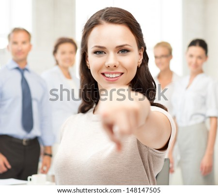 business concept - attractive young businesswoman pointing at you in office - stock photo