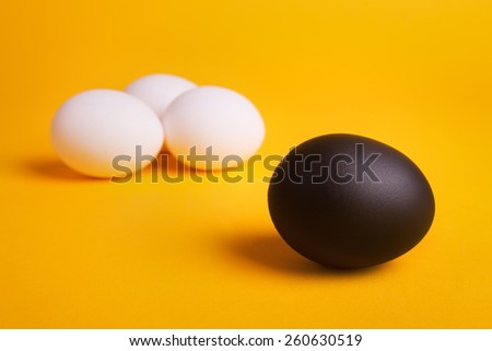 business concept background with a black egg surrounded by normal eggs
