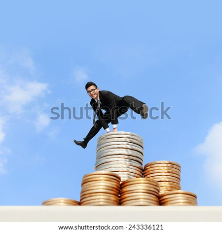 business concept - business man run and jump on money stairs with blue sky background, asian male - stock photo