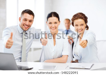 business concept - business team showing thumbs up in office - stock photo