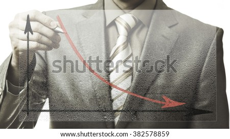 business concept. businessman drawing a graph down on corrugated glass