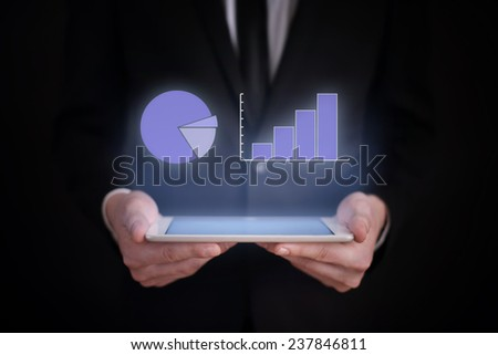 business concept. businessman holding a tablet with the projection of the  data analysis graph above the screen. financial growth. - stock photo