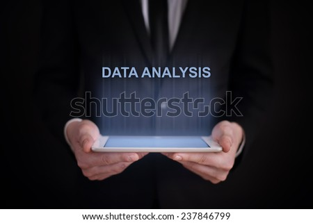 business concept. businessman holding a tablet with the projection of the  text data analysis - stock photo