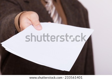 Business concept. Businessman holding empty poster sheet of paper, copy space for text. Male hands with blank advertisement card. - stock photo