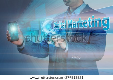 Business concept. Businessman holding smatrfon and click on the virtual display with text digital marketing. - stock photo