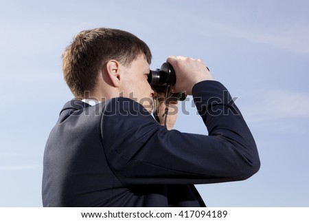 Business concept. Businessman looks through a binoculars - stock photo