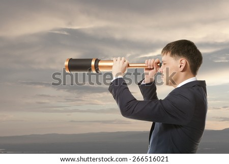 Business concept. Businessman looks through a telescope - stock photo
