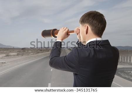 Business concept. Businessman looks through a telescope  - stock photo