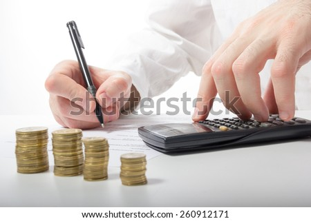 Business concept. Businessman's hand counting money on calculator and signing documents at office workplace, office work. Stack of coins. Financial Accounting - money and calculator. - stock photo