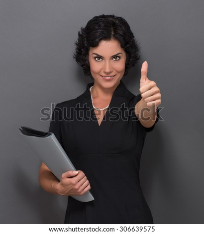 Business concept. Businesswoman showing thumb-up over grey background. Lady in business black dress holding documents and smiling for the camera. - stock photo