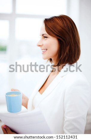 business concept - businesswoman with cup of coffee and papers in office
