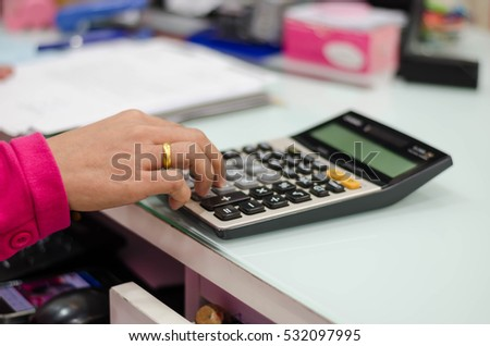 Business concept - businesswoman working with calculator in office.