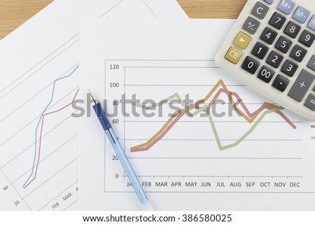 Business concept : Calculator, and blue pen on graph background.
