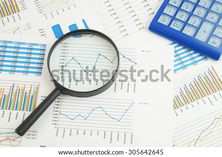Business concept, calculator and magnifying glass on financial charts and graphs