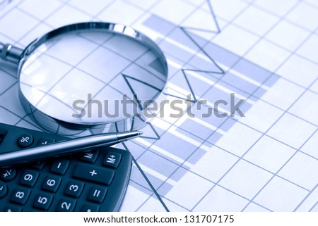 Business concept. Calculator and pen near magnifying glass on paper background with chart - stock photo